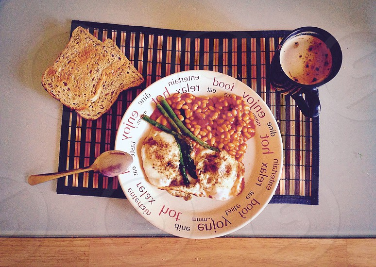beans eggs in the plate with toasted bread and a coffee photo