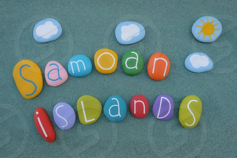 Samoan Islands souvenir with a composition of colored stones over green sand photo