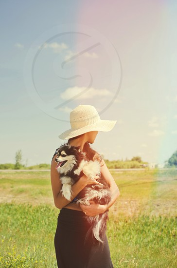 Woman outdoors with small dog in arms light leak effect. photo