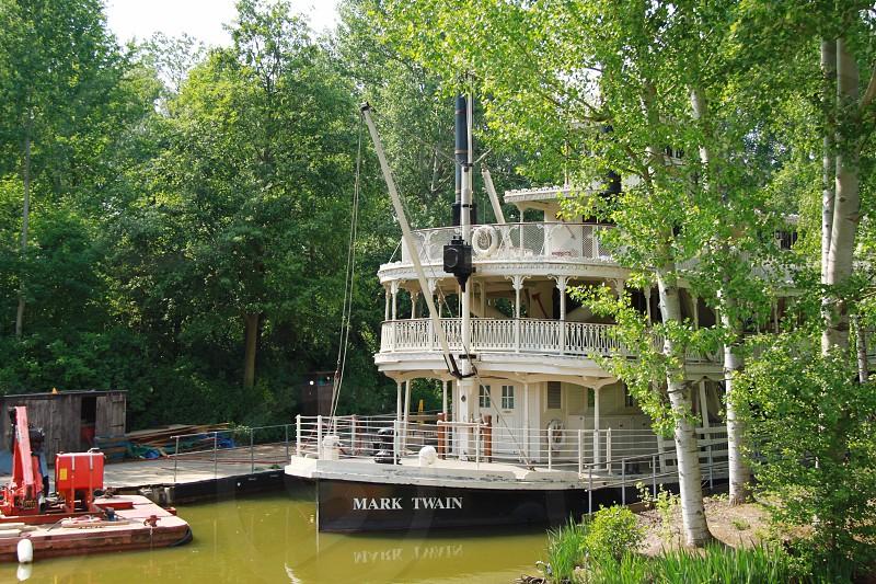 white and black Mark Twain boat near green leaf tree photo