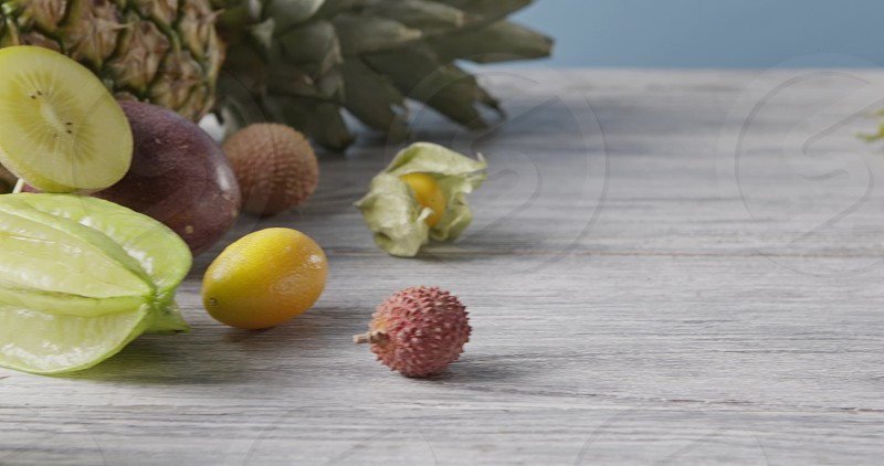 Fresh organic exotic tropic fruits on a wooden gray table on a blue background. Panoramic motion 4K UHD video 3840 2160p. Vegetarian healthy concept. photo