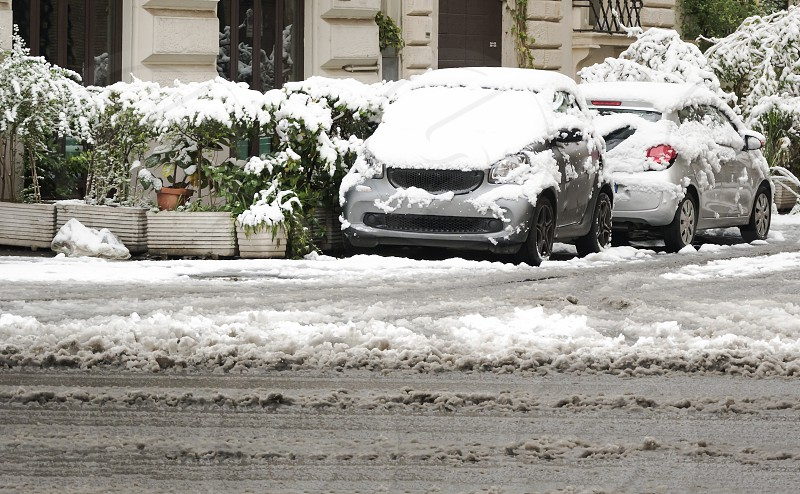 cars parked in the city almost completely covered with snow. winter and cold temperature concept photo