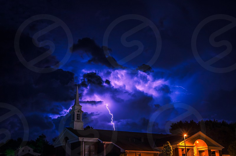 purple lightning over white painted house photo