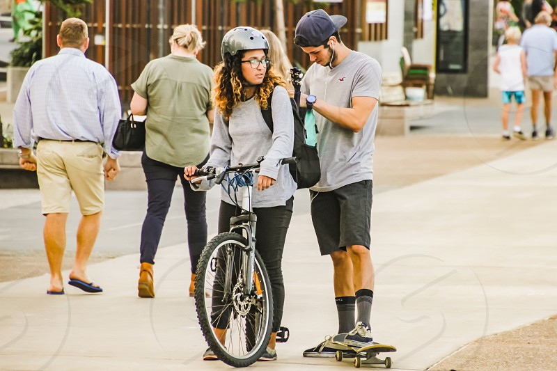 young couple with a bicycle and skateboard on a city street photo