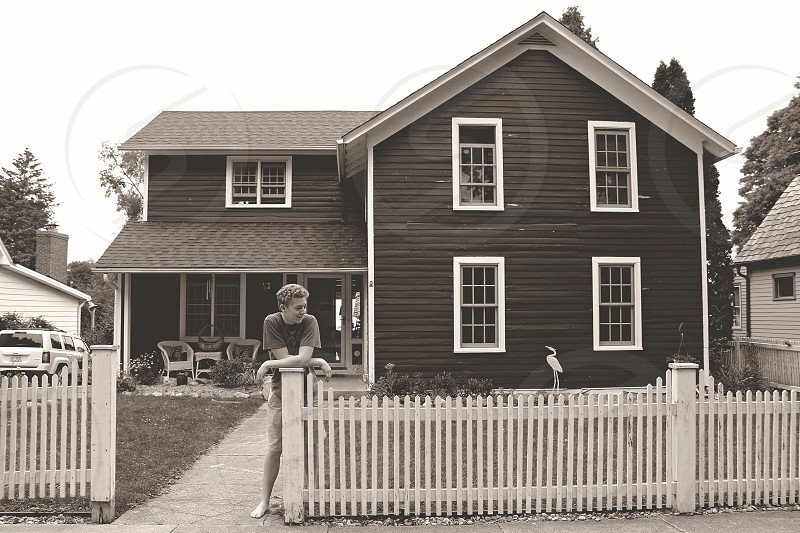 gray and white cape cod house with white picket fence and boy leaning on fence post photo