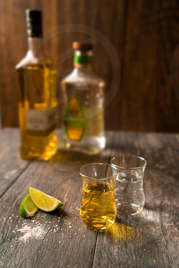Two shot glasses of tequila and their bottle on a wooden background photo