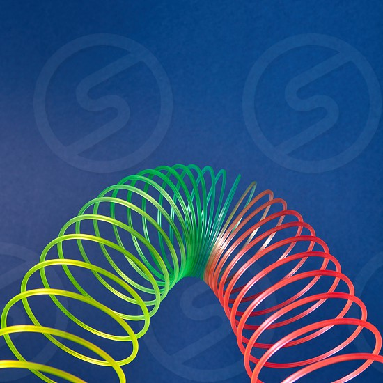 Flexible rainbow plastic spring in a form of parabola on a blue background with place for text. photo