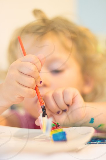 girl painting a toy on table photo