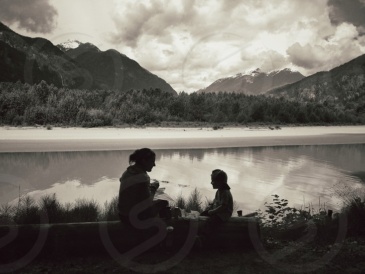 Boy and woman seated on log with mountain and river view in background photo