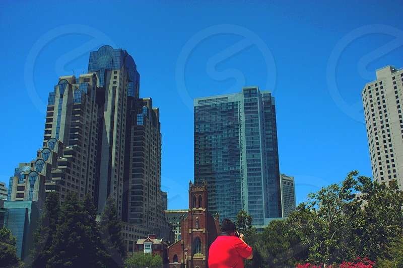 woman in red t shirt taking photo of high rise buildings photo