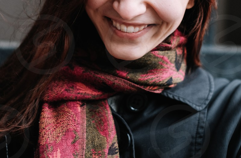 smiling red hair woman wearing a red scarf and black jacket photo