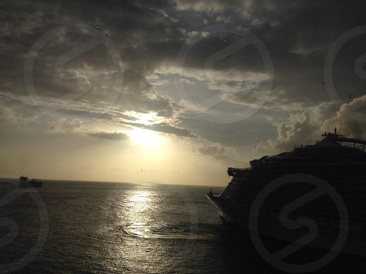 white cruise ship on grey ocean beneath white gray cloudy sky photo