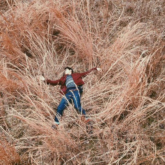 person in brown jacket lying on dried grass photo