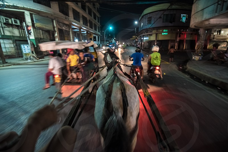 person riding carriage walking on the street during nightime photo