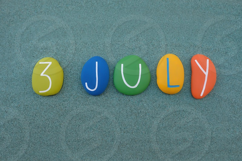 3 July calendar date composed with multi colored stones over green sand photo