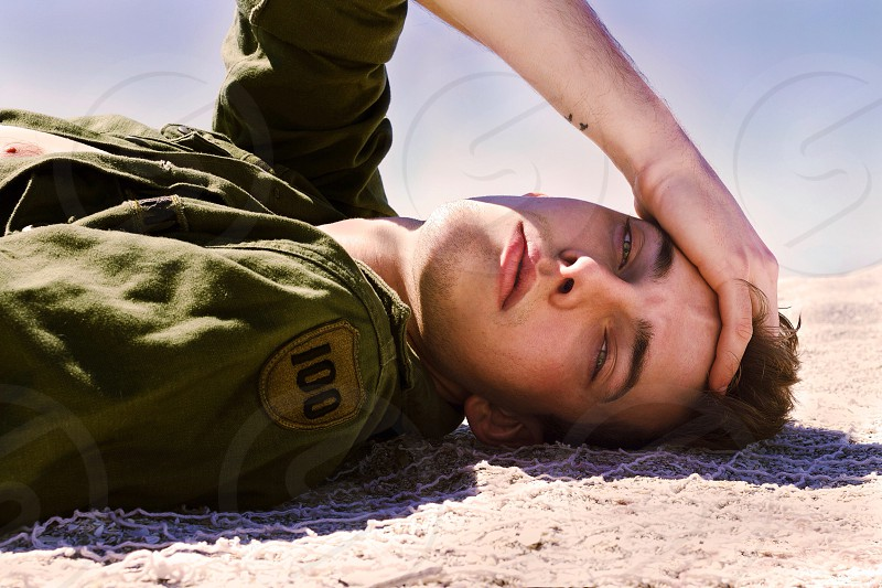 man in army green oxford shirt lying in the sand photo