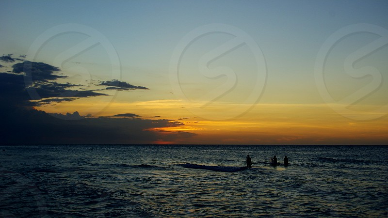 People enjoying the sea at sunset photo