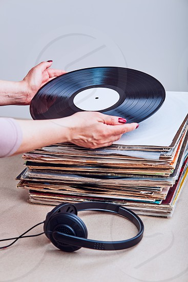 Woman taking vinyl from stack of many black vinyl records headphones put at the front of vinyls. Copy space for text. Candid people real moments authentic situations photo