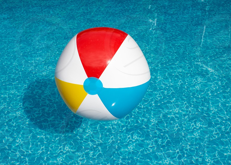 Beach ball floating on water in outdoor swimming pool on a sunny day. photo