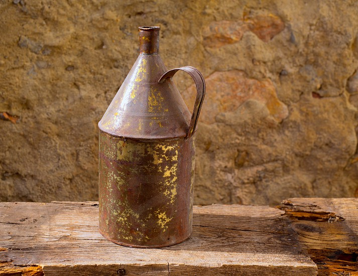 Antique rusted iron jar with aged brass on vintage wood self photo