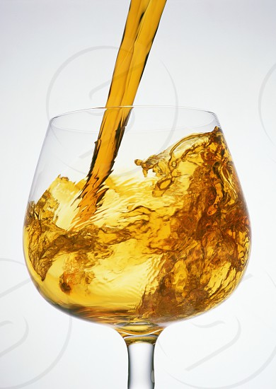 Pour the whiskey into the glass. photo