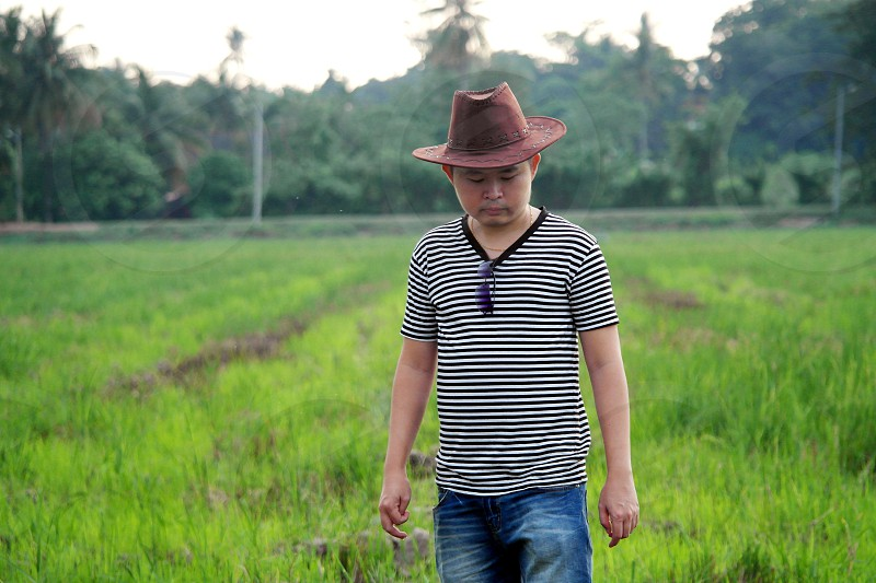 man wearing brown hat and black and white stripe v neck t shirt standing on green grass field under clear sky during daytime photo