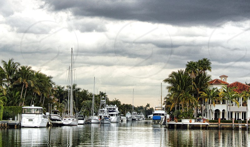 Yachts and boats are docked in a canal under a cloudy sky photo