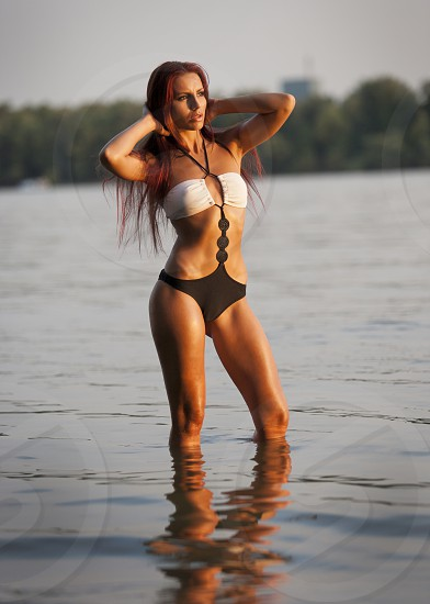 Red hair young woman in water in swimming suit photo