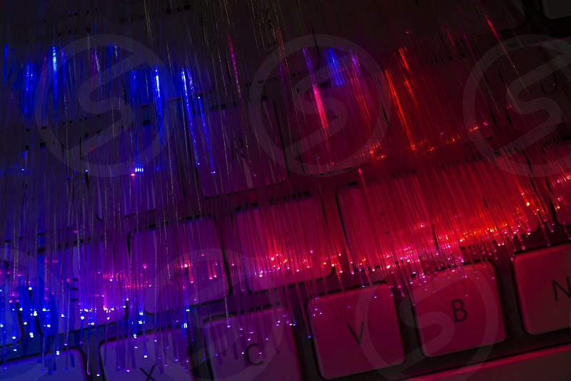 Colourful optic fibers illuminated on keyboard. High speed internet concept. Data transfer optic fiber cable. Bunch of many optical fibers glowing different colors. Technology background. photo