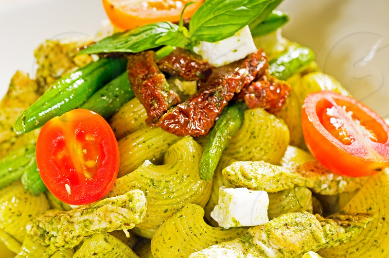 fresh lumaconi pasta and pesto sauce with vegetables and sundried tomatoestipycal italian food photo