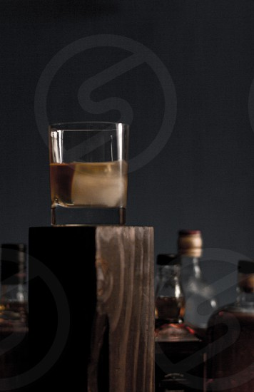 drinking glass on top of brown wooden rectangular stand near glass whisky bottle photo