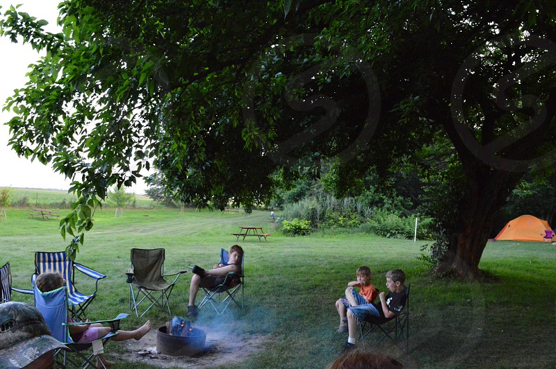 kids in fold out chairs surrounding campfire in grassy field near tree photo