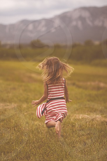 Barefoot and running in an open summer field photo