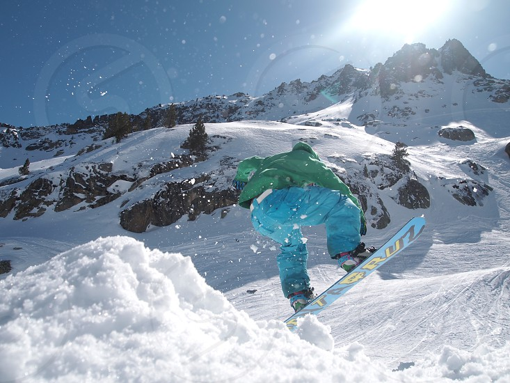 person in green jacket and blue pants outfit doing a snow ski flip on side of snowy mountain at daytime photo