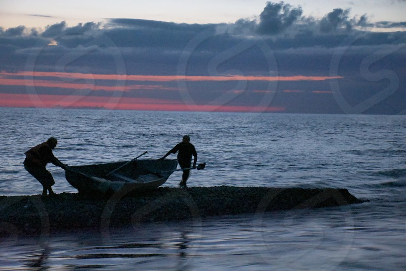 2 people holding canoe near dock with small waves of sea under clouded sky photo