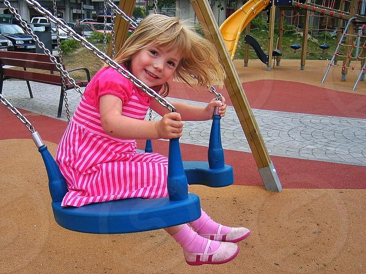 girl wearing pink stripe dress sitting on a swing photo