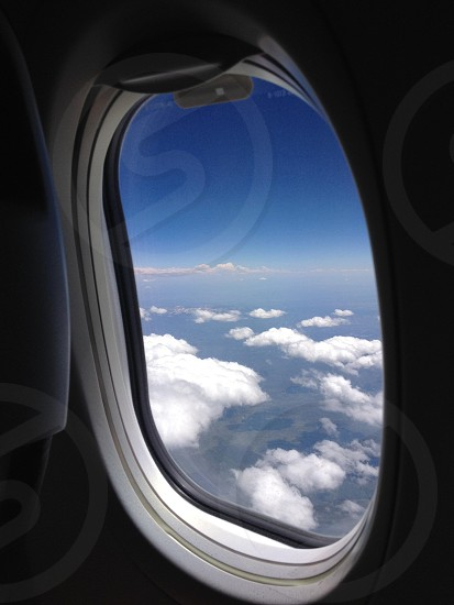 airplane window open showing top view of clouds photo