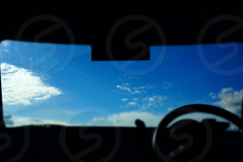 blue and white sky viewed from a parked car windshield photo