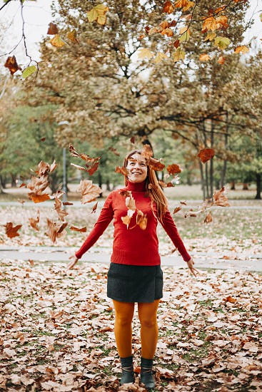 Young woman throwing autumn leaves in the air in the park photo