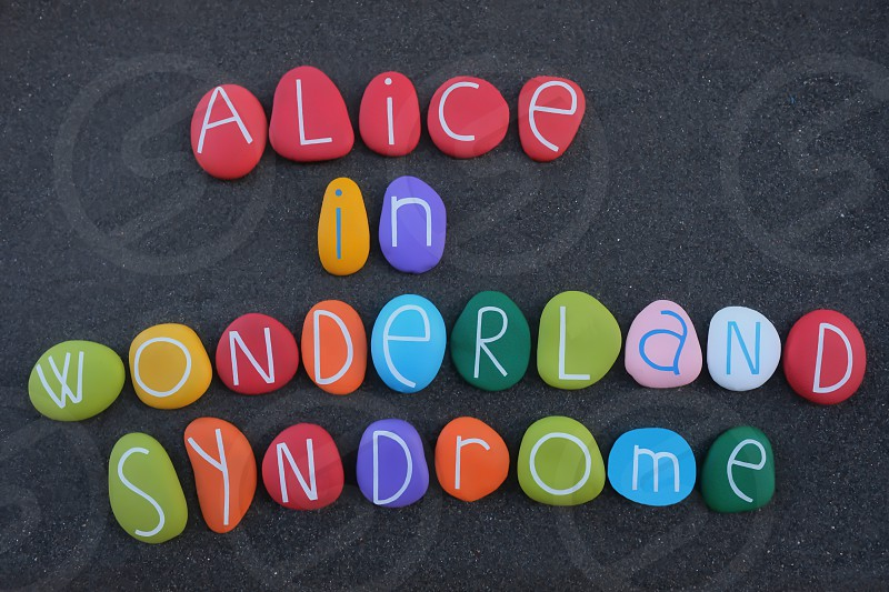 Alice in Wonderland syndrome  neuropsychological condition that distorts perception. Creative syndrome name composed with multi colored stone letters over black sand photo