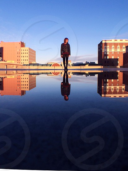 woman in black leather jacket standing on top of building photo