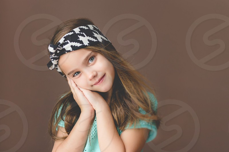 Little girl with headband smiling and posing in natural light  photo