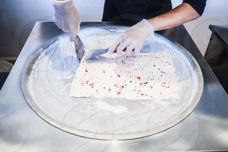 man in black long sleeve shirt and white rubber gloves holding metal spatula over round stainless steel platter with rectangular white and red speckled pastry photo