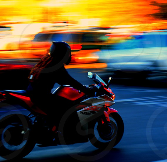 "Slow shutter tracking shot of a motorcyclist. Heavy motion blur on background subject I as in focus and clear. Developed with Darktable (tm) in a high contrast ""neon"" style. photo"