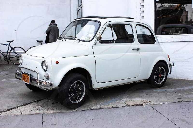 white fiat 500 beside road near person standing near wall during daytime photo