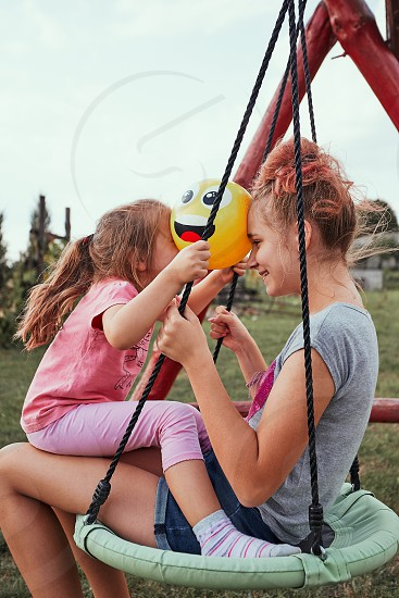 Teenage girl playing with her younger sister in a home playground in a backyard. Happy smiling sisters having fun on a swing together on summer day. Real people authentic situations photo