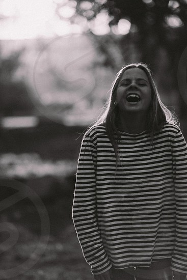woman in black and white stripe sweater laughing photo