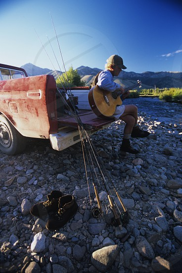 Fly fisherman playing guitar on old truck by river photo