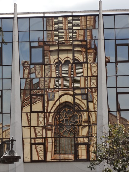Reflection of an Old World cathedral on the glass wall of a modern building on a Caribbean island. photo