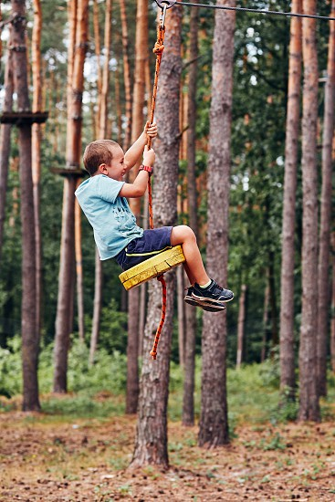 Happy boy riding on the zip line in rope park in forest while spending summer vacation. Real people authentic situations photo